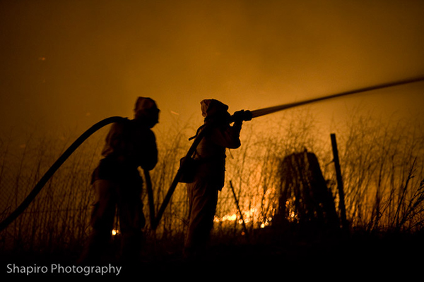 silhouette of firemen with hose lie