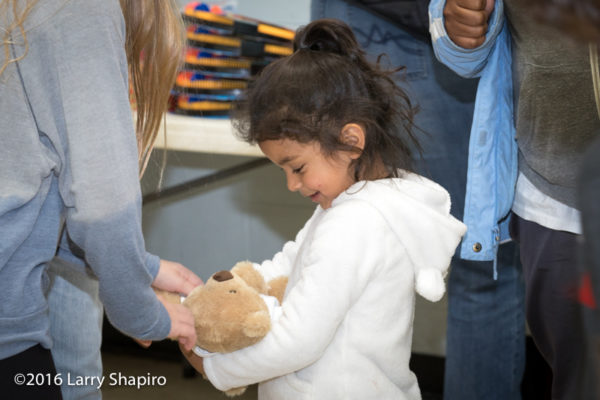 young girl receives a teddy bear on Thanksgiving