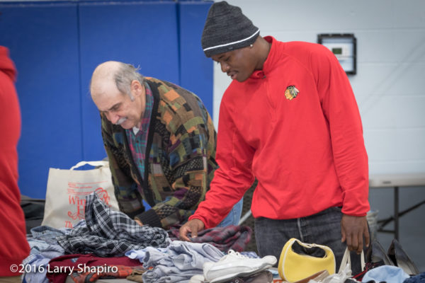 men looking through donated clothing on Thanksgiving
