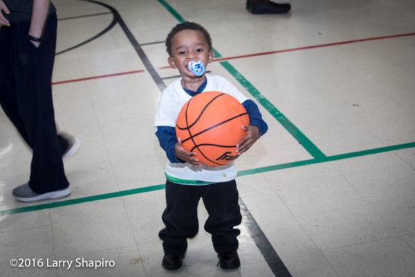young boy with large basketball