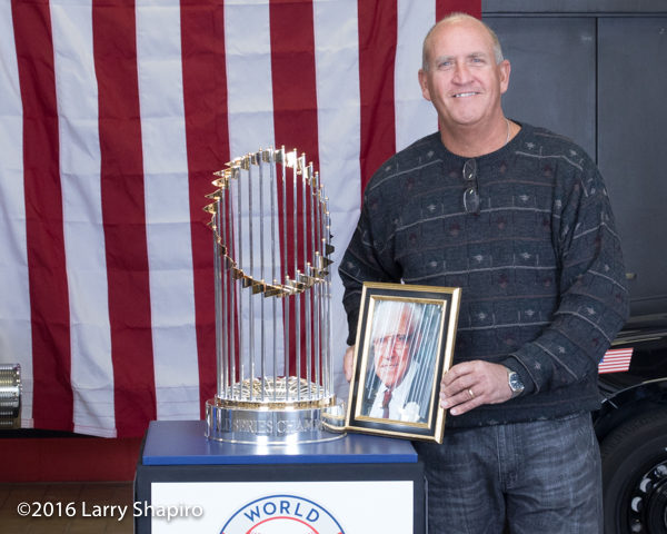 man with photo of deceased father posing with the world series championship trophy