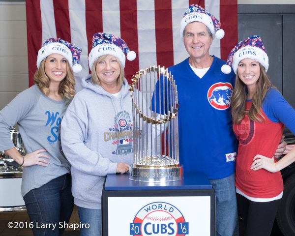 family posing with the world series trophy