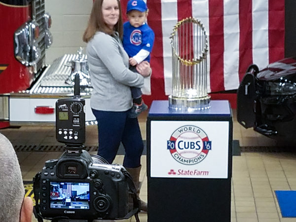 photo being taken of a mother and toddler with the World Series championship trophy