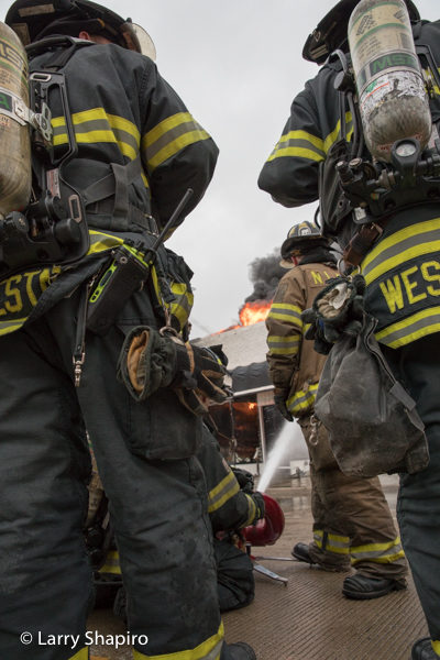 Firefighters standing by at a building fire
